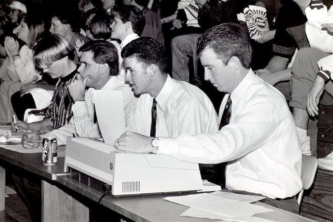 Mike Kirk (far right) keeping stats at a basketball game in the 1990's. Photo courtesy UCO Sports Info.